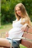 Mujer feliz del embarazo en banco Foto de archivo libre de regalías