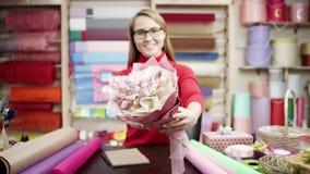 Mujer feliz del florista en el puente rojo que envuelve las flores en papel en la floristería Ella intenta componer las flores en almacen de video