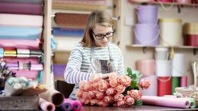 Mujer feliz del florista que envuelve las flores en papel en la floristería Ella intenta componer las flores en un ramo hermoso almacen de video