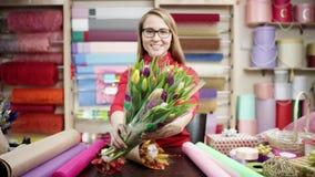 Mujer feliz del florista que envuelve las flores en papel en la floristería Ella intenta componer las flores en un ramo hermoso metrajes