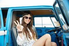 Mujer feliz del hippie que muestra paz en coche del minivan Fotografía de archivo