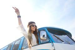 Mujer feliz del hippie que muestra paz en coche del minivan Imágenes de archivo libres de regalías