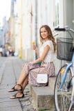 Mujer feliz del inconformista con la bici que come el helado Fotos de archivo
