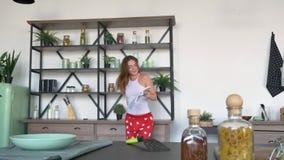 Mujer feliz del jengibre en pijamas que lee el libro culinario y que baila en la cocina moderna, receta femenina hermosa de la le almacen de metraje de vídeo