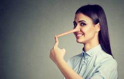 Mujer feliz del mentiroso con la nariz larga foto de archivo