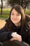 Mujer feliz del oung que se sienta en un banco fotografía de archivo libre de regalías