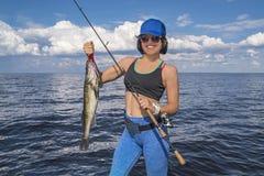 Mujer feliz del pescador con el trofeo de los pescados del zander en el barco foto de archivo libre de regalías
