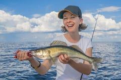 Mujer feliz del pescador con el trofeo de los pescados del zander en el barco foto de archivo