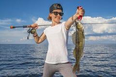 Mujer feliz del pescador con el trofeo de los pescados del zander en el barco imagen de archivo libre de regalías