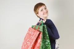 Mujer feliz del redhead con los bolsos de compras Foto de archivo libre de regalías