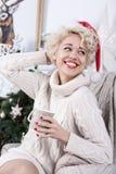 Mujer feliz del sombrero de Papá Noel de la Navidad que se sienta en una silla imagenes de archivo