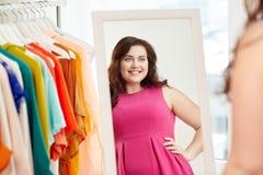 Mujer feliz del tamaño extra grande que presenta en casa el espejo Imágenes de archivo libres de regalías