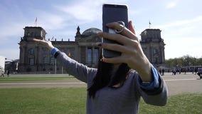 Mujer feliz del viaje que hace la llamada video en Smartphone, edificio de Reichstag, Berlín almacen de metraje de vídeo