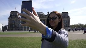 Mujer feliz del viaje que hace la llamada video en Smartphone, edificio de Reichstag, Berlín metrajes