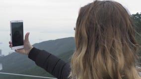 Mujer feliz del viaje que toma la foto del selfie en el teléfono móvil en Victoria máxima en la ciudad de Hong Kong, China El hac metrajes
