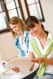 Mujer feliz dos del estudiante en el país - con la computadora portátil Imagen de archivo libre de regalías