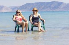 Mujer feliz dos que se relaja en la playa junto fotos de archivo