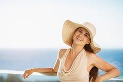 Mujer feliz el las vacaciones que se colocan en balcón fotos de archivo