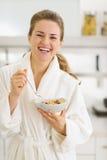 Mujer feliz en albornoz que come el desayuno sano Imágenes de archivo libres de regalías