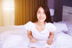 Mujer feliz en cama en dormitorio Fotografía de archivo libre de regalías