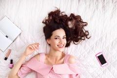 Mujer feliz en cama que sonríe en la opinión superior de la cámara Imágenes de archivo libres de regalías