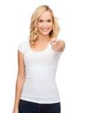 Mujer feliz en camiseta blanca en blanco que señala en usted Fotografía de archivo libre de regalías