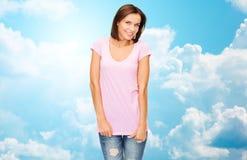 Mujer feliz en camiseta blanca en blanco sobre el cielo azul Imagen de archivo