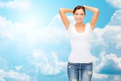 Mujer feliz en camiseta blanca en blanco sobre el cielo azul Imagen de archivo libre de regalías