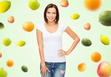 Mujer feliz en camiseta blanca en blanco sobre las frutas Imagenes de archivo