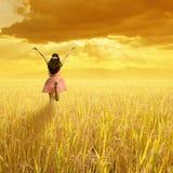Mujer feliz en campo del arroz con la montaña y la puesta del sol Foto de archivo libre de regalías