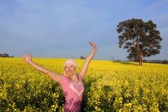 Mujer feliz en campo del canola de oro Foto de archivo