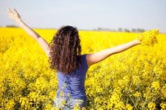 Mujer feliz en campo del canola en día soleado Foto de archivo libre de regalías