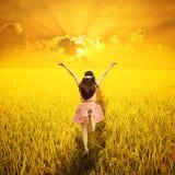Mujer feliz en campo y puesta del sol del arroz Foto de archivo libre de regalías