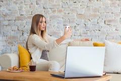 Mujer feliz en casa que se sienta en el sofá y que hace el selfie Freelancer, ordenador Foto de archivo