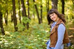Mujer feliz en chaqueta roja en el bosque Fotos de archivo