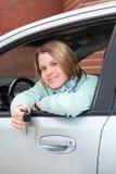 Mujer feliz en coche con clave de ignición Foto de archivo libre de regalías