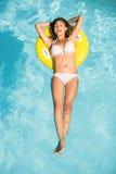 Mujer feliz en el bikini blanco que flota en el tubo inflable en piscina Foto de archivo