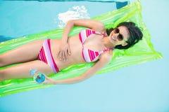 Mujer feliz en el bikini que miente en cama de aire en piscina Fotos de archivo