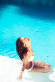 Mujer feliz en el bikini que se sienta por el lado de la piscina Foto de archivo