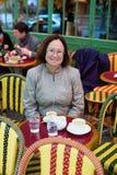 Mujer feliz en el café de consumición de París Imágenes de archivo libres de regalías