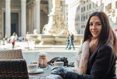 Mujer feliz en el café de la calle de la mañana que se sienta en Roma en frente Foto de archivo libre de regalías