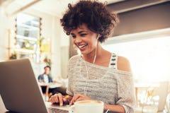 Mujer feliz en el café usando el ordenador portátil Imagen de archivo