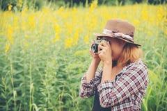 Mujer feliz en el campo de flor amarillo hloding con la cámara retra hacia fuera Imágenes de archivo libres de regalías