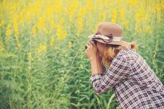Mujer feliz en el campo de flor amarillo hloding con la cámara retra hacia fuera Imagen de archivo libre de regalías