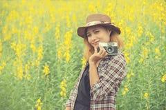 Mujer feliz en el campo de flor amarillo hloding con la cámara retra hacia fuera Foto de archivo