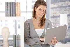 Mujer feliz en el estante para libros con el ordenador Fotos de archivo
