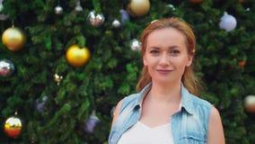 Mujer feliz en el fondo del árbol de navidad y de las palmeras en una ciudad tropical El concepto del viaje del Año Nuevo imagen de archivo