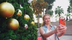 Mujer feliz en el fondo del árbol de navidad y de las palmeras en una ciudad tropical El concepto del viaje del Año Nuevo imagenes de archivo