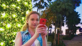 Mujer feliz en el fondo del árbol de navidad y de las palmeras en una ciudad tropical El concepto del viaje del Año Nuevo fotos de archivo