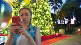 Mujer feliz en el fondo del árbol de navidad y de las palmeras en una ciudad tropical El concepto del viaje del Año Nuevo foto de archivo libre de regalías